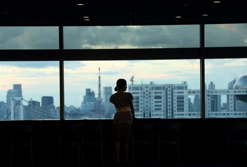 A woman looks out of a window at the observatory of a building in Tokyo, Japan