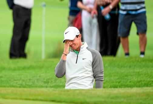 Rory McIlroy reacts after hitting a shot from the bunker on to the 11th green during day one of the Irish Open at Fota Island. Photo: Matt Browne / SPORTSFILE