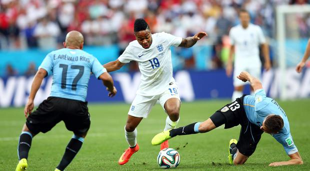 England winger Raheem Sterling gets past a tackle from Jose Gimenez of Uruguay. Photo: Julian Finney/Getty Images