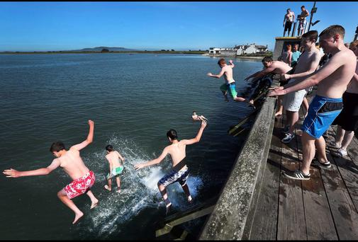 Teenagers jumping off the boardwalk bridge at Dollymount yesterday during the warm weather. Pic Steve Humphreys 18th June 2014.