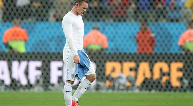 A dejected Wayne Rooney leaves the pitch after England's defeat against Uruguay. Photo: Mike Egerton/PA Wire