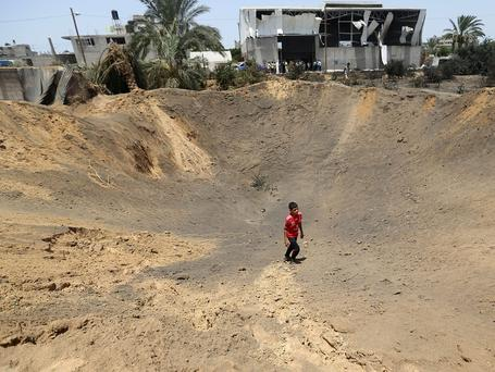 A Palestinian man walks inside a crater made by an Israeli airstrike as others watch in Gaza City. The Israeli military said it carried out airstrikes on in Gaza overnight, in retaliation to several rockets fired by Gaza militants at Israel. The army said it targeted sites from where rockets had been launched and a weapons storage facility. Picture credit: AP Photo/Hatem Moussa