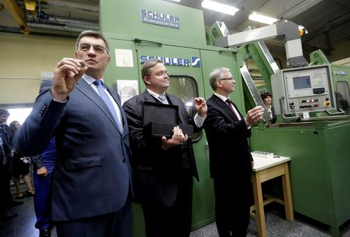 Lithuania's Prime Minister Algirdas Butkevicius (L-R), central bank governor Vitas Vasilauskas and Minister of Finance Rimantas Sadzius show off Lithuanian 1 euro coins to the media in the Lithuanian Mint in Vilnius June 16, 2014. The first Lithuanian euro coins are being minted before the country will join the euro zone on January 1, 2015. REUTERS/Ints Kalnins (LATVIA - Tags: POLITICS BUSINESS)
