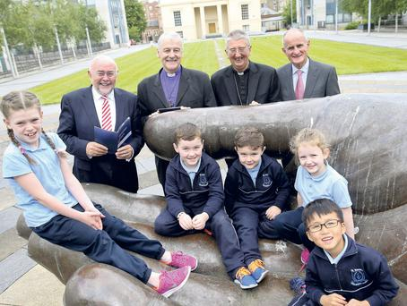 Ruairi Quinn, Archbishop Michael Jackson, Archbishop Diarmuid Martin and Dr Martin McAleese with Macy Lynam (8), Preston Sheridan (7), Sam Sheridan (5), Aliyah Lynan (8) and Daniel Li (6) from St Vincent's School at the launch of the report