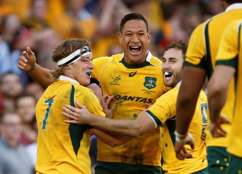 Australia's Wallabies Israel Folau (C) celebrates his second try with team captain Michael Hooper (L) and scrumhalf Nic White in the second half of their international rugby game against France in Sydney, June 21, 2014. Australia defeated France 39-13 in Sydney on Saturday to clean sweep the three-test series, displaying an expansive game, which saw the Wallabies dominate possession and territory. REUTERS/Jason Reed