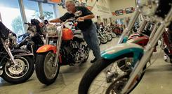 A salesman pushes a Harley Davidson motorcycle to a parking spot at a Miami dealership