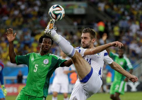 Bosnia's Tino-Sven Susic, right, kicks the ball clear from Nigeria's Efe Ambrose during the group F World Cup soccer match between Nigeria and Bosnia at the Arena Pantanal in Cuiaba, Brazil, Saturday, June 21, 2014. (AP Photo/Dolores Ochoa)