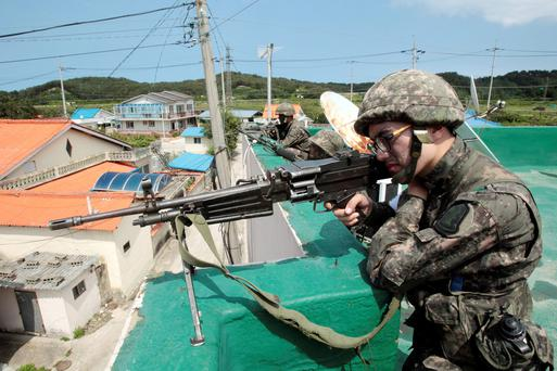 South Korean army soldiers aim their machine guns as they search for a South Korean conscript soldier who is on the run after a shooting incident in Goseong, South Korea, Sunday, June 22, 2014. South Korean military authorities have surrounded a soldier who fled his border outpost after killing five comrades the day before and were trying to persuade him to surrender, a defense official said Sunday.(AP Photo/Ahn Young-joon)