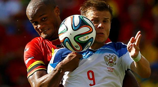 Belgium's Vincent Kompany fights for the ball with Russia's Alexander Kokorin