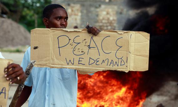 A resident holds a placard as he participates in a protest against the recent attack by unidentified gunmen in the coastal Kenyan town of Mpeketoni, June 17, 2014. Kenya's President Uhuru Kenyatta said on Tuesday that two days of attacks on the coast in which about 65 people were killed were planned by