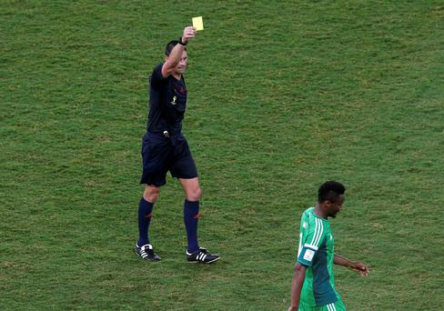 Referee Peter O' Leary of New Zealand shows Nigeria's John Mikel Obi the yellow card during the 2014 World Cup Group F soccer match between Nigeria and Bosnia