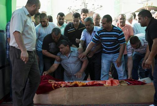 The father of Mohammed Qaraqara kneels next to his coffin during his funeral in the northern town of Arabeh. An attack from inside Syria on Sunday killed a 13-year-old Israeli boy, Qaraqara, on the occupied Golan Heights, the first fatality on Israel's side of the frontier since the Syrian civil war began, relatives and the military said. Photo credit: REUTERS/Baz Ratner