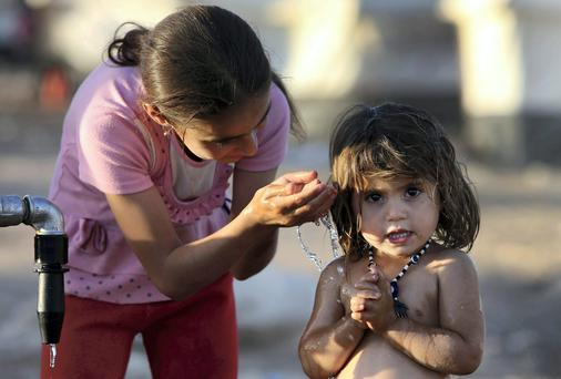 An Iraqi girl bathes her younger sister at a camp for displaced Iraqis who fled from Mosul and other towns, in the Khazer area outside of Irbil, northern Iraq. U.S. Secretary of State John Kerry flew to Baghdad on Monday to meet with Iraq's leaders and personally urge the Shiite-led government to give more power to political opponents before a Sunni insurgency seizes more control across the country and sweeps away hopes for lasting peace. (AP Photo/Hussein Malla)
