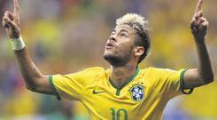 BRASILIA, BRAZIL - JUNE 23: Neymar of Brazil celebrates scoring his team's second goal and his second of the game during the 2014 FIFA World Cup Brazil Group A match between Cameroon and Brazil at Estadio Nacional on June 23, 2014 in Brasilia, Brazil. (Photo by Clive Brunskill/Getty Images)