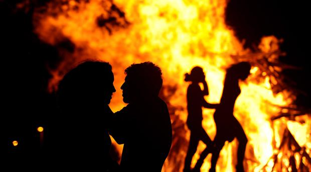 People attend a party held during the night of the San Juan bonfire on the beach of Playa de Poniente in Gijon early June 24, 2014. Fires formed by burning unwanted furniture, old school books, wood and effigies of malign spirits are seen across Spain as people celebrate the night of San Juan, a purification ceremony coinciding with the summer solstice. Reuters/Eloy Alonso