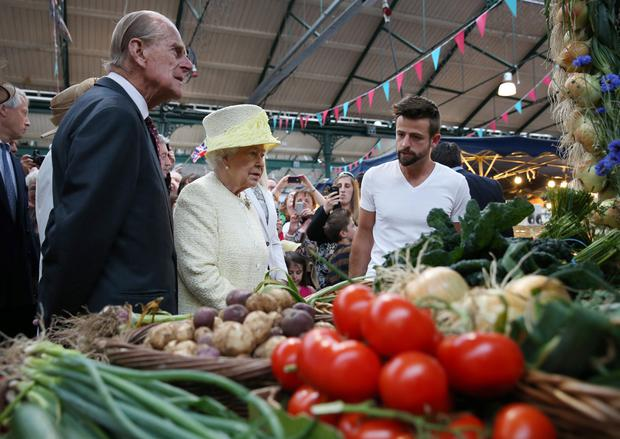Queen Elizabeth II and the Duke of Edinburgh (left) talk with stall holder Simon Matthews during a walk around St. Georges Market in Belfast