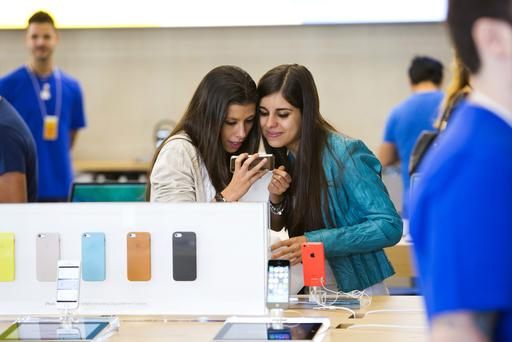 Customers try an Apple Inc. iPhone 5s during the opening of Apple Inc.'s new Spanish flagship store in Madrid over the weekend.