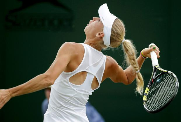 Caroline Wozniacki of Denmark hits a return to Shahar Peer of Israel in their women's singles tennis match at Wimbledon
