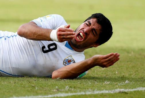 Uruguay's Luis Suarez reacts after clashing with Italy's Giorgio Chiellini