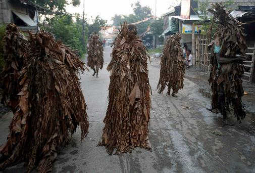 Residents, covered with dried banana leaves and mud, walk along a road as they participate in a religious ritual known locally as