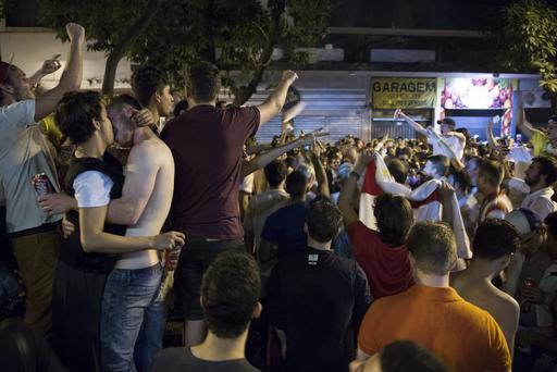 BELO HORIZONTE, BRAZIL - JUNE 24: A couple kiss as fans of the England football team sing and dance outside bars in the centre of Belo Horizonte after watching England play Costa Rica on June 24, 2014 in Belo Horizonte, Brazil. England drew 0-0 with Costa Rica in their final game of Group D in the 2014 FIFA World Cup, the result sees England finish at the bottom of the group table with Costa Rica at the top. (Photo by Oli Scarff/Getty Images)