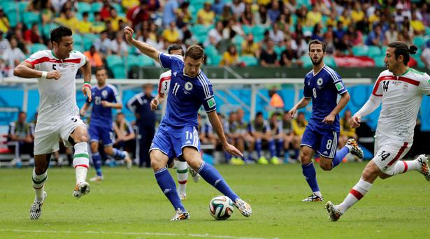 Bosnia's Edin Dzeko, center, scores the opening goal during a group F World Cup soccer match between Bosnia and Iran at the Arena Fonte Nova in Salvador