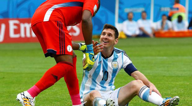 Nigeria's goalkeeper Vincent Enyeama (L) helps Argentina's Lionel Messi up during their 2014 World Cup Group F soccer match at the Beira Rio stadium in Porto Alegre