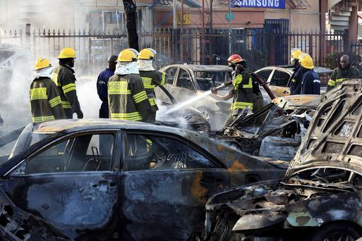 Firefighters douse cars after a bomb blast at a crowded shopping district in Abuja
