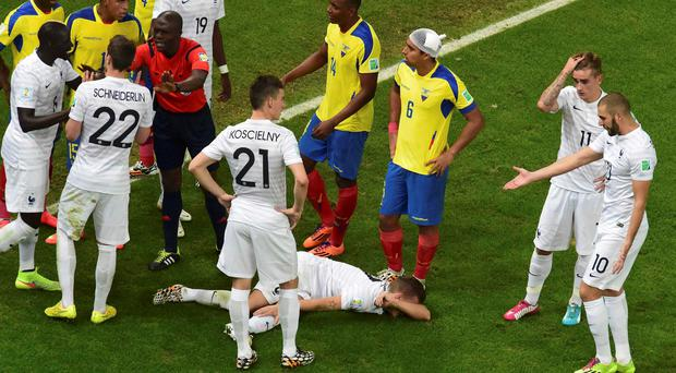 France's Lucas Digne lies on the pitch after being fouled by Ecuador's Antonio Valencia during their 2014 World Cup Group E soccer match at the Maracana stadium in Rio de Janeiro