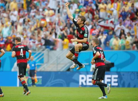 Germany's Thomas Mueller (C) celebrates past his teammates Toni Kroos (R) and Benedikt Hoewedes after scoring a goal against the U.S.