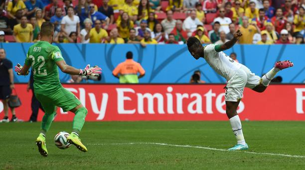Ghana's Asamoah Gyan, right, scores his side's first goal past Portugal goalkeeper Beto during the group G World Cup soccer match between Portugal and Ghana at the Estadio Nacional in Brasilia