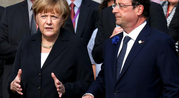 Germany's Chancellor Angela Merkel talks to France's President Francois Hollande