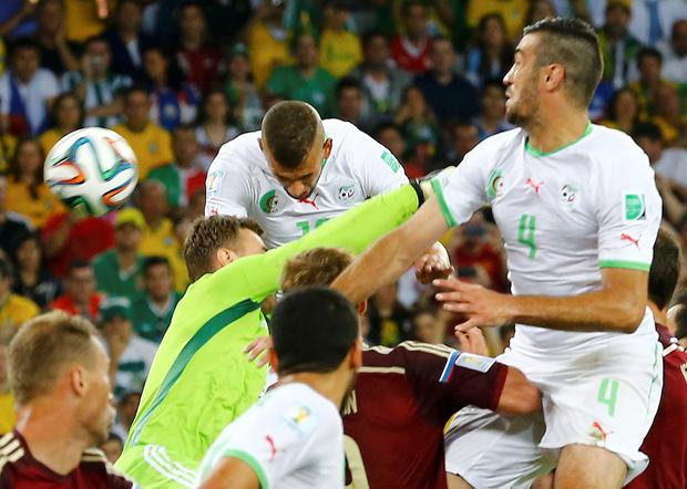 Algeria's Islam Slimani (top L) heads the ball to score a goal against Russia during their 2014 World Cup Group H soccer match at the Baixada arena in Curitiba