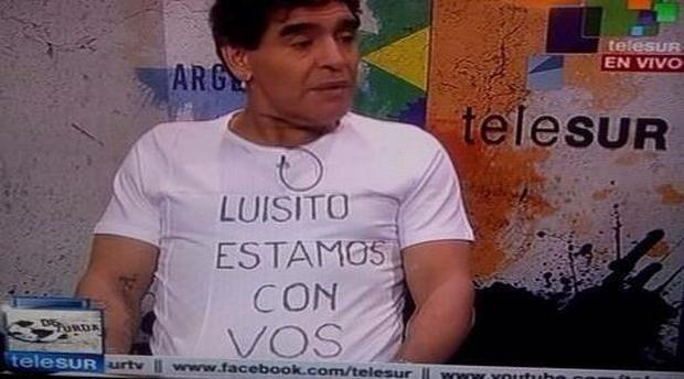 Diego Maradona wears a t-shirt in support of Luis Suarez
