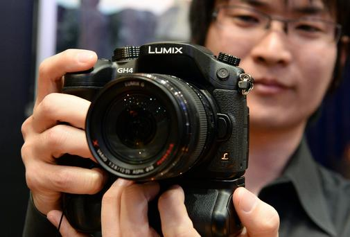 A Panasonic employee shows off the company's latest flagship camera, Lumix GH4 during