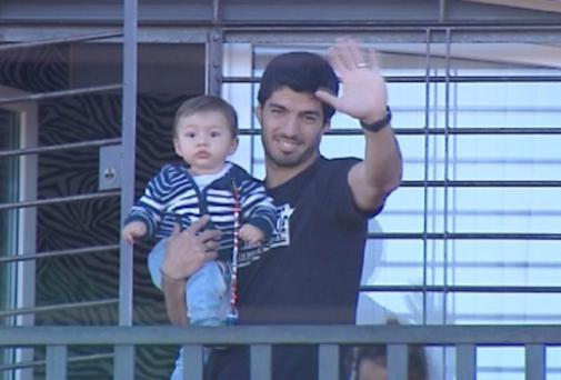 Luis Suarez holds his son Benjamin near Montevideo, Uruguay, yesterday. Photo credit: REUTERS/Television Nacional Uruguay