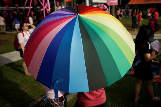 Participants shield themselves from the sun under a rainbow-coloured umbrella before taking part in the forming of a giant pink dot at the Speakers' Corner in Hong Lim Park in Singapore