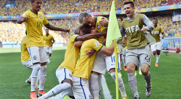 Brazil's David Luiz, centre, celebrates with teammates after Brazil's opening goal during the World Cup round of 16 soccer match between Brazil and Chile at the Mineirao Stadium in Belo Horizonte