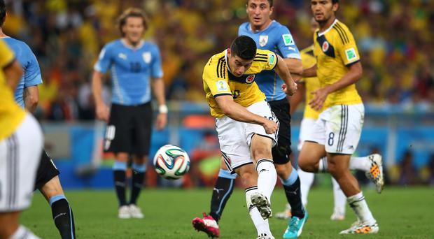 James Rodriguez of Colombia shoots and scores his team's first goal during the 2014 FIFA World Cup Brazil round of 16 match between Colombia and Uruguay at the Maracana