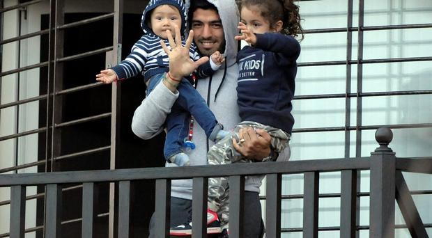 Luis Suarez holds his children on the balcony of his home on the outskirts of Montevideo as he greets fans after returning to Uruguay after his banishment from the World Cup. Photo: AP Photo/Matilde Campodonico