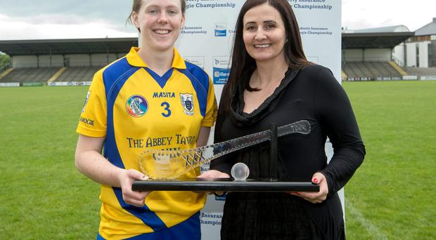 Clare's Marie McGrath is presented with the player of the match award by Annette Ni Dhathlaoi, head of Marketing Liberty Insurance, after the Camogie Championship clash with Offaly. Photo: INPHO/James Crombie