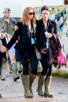 British designer Stella McCartney, left, walks with her sister Mary, at Glastonbury. (Photo by Jonathan Short/Invision/AP)