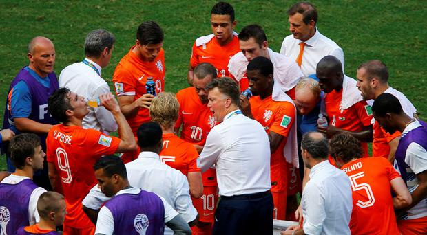 Netherlands coach Louis van Gaal speaks to his players during a cooling break in their 2014 World Cup round of 16 game against Mexico at the Castelao arena in Fortaleza