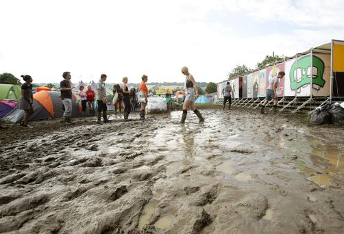Festival goers in the mud, at the Glastonbury Festival. PA