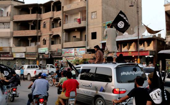 Members loyal to the Islamic State in Iraq and the Levant (ISIL) wave ISIL flags as they drive around Raqqa. Reuters