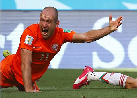 Arjen Robben of the Netherlands reacts after being tackled by Mexico's Miguel Layun during their 2014 World Cup round of 16 game at the Castelao arena in Fortaleza