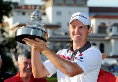 Justin Rose, of England, poses with the trophy after he won the Quicken Loans National golf tournament
