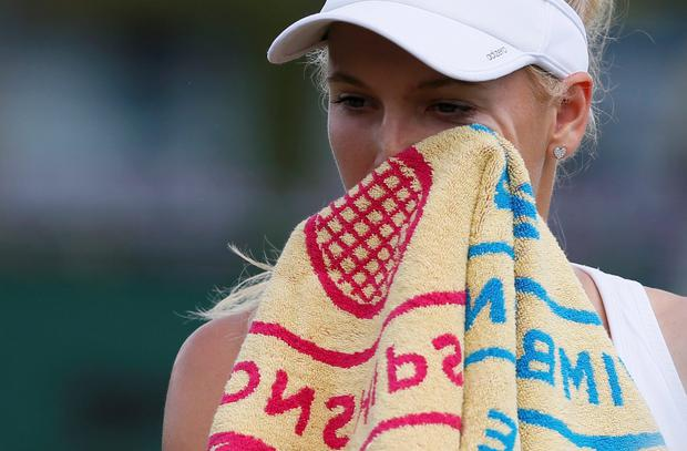 Caroline Wozniacki of Denmark wipes her face during her women's singles tennis match defeat to Barbora Zahlavova Strycova of the Czech Republic