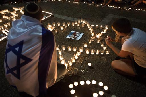 Israelis light candles in Tel Aviv's Rabin Square, as they mourn the death of three teenagers who were abducted June 30, 2014