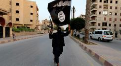 A member loyal to the Islamic State in Iraq and the Levant (ISIL) waves an ISIL flag in Raqqa. The offshoot of al Qaeda which has captured swathes of territory in Iraq and Syria has declared itself an Islamic